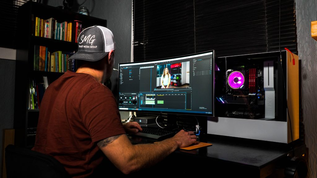 Guy in front of the computer editing a video with music